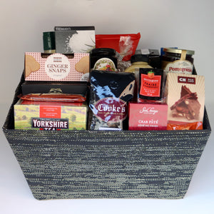 A sequined grey rectangular basket holding a selection of products, including: a jar of jelly, a jar of jam, a 1-pound bag of Cooke's coffee, a tin of crab paté, a box of truffles, a box of tea, a bag of candy, a box of cookies, a box of chocolate, a jar of mustard, a bottle of olive oil, and 2 assorted chocolate bars. Exact products vary by order.