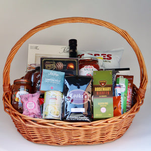 A large wicker basket with handle, holding a selection of products including: a jar of jam, a jar of chutney, a box of pasta, a box of Rogers chocolates, a can of anchovies, a 1-pound bag of Cooke's coffee, a tin of lobster paté, a bag of risotto, a jar of pasta sauce, a bag of chips, a bottle of olive oil, a sleeve of mints, a sleeve of cookies, and 4 assorted chocolate bars.. Exact products vary by order.