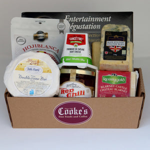 A brown rectangular basket with the burgundy Cooke's logo holding a selection of products, including: a jar of jelly, a bag of olives, a piece of blue cheese, a wheel of brie, a block of Cooke's cheddar, a block of gouda, a container of goat cheese, and a box of crackers. Exact products vary by order.