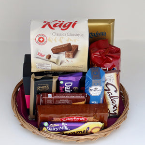 A thin wicker tray holding a selection of products, including: a bag of chocolate wafer cookies, two sleeves of chocolate cookies, 6 assorted chocolate bars, a box of truffles, and a package of chocolate pastilles. Exact products vary by order.