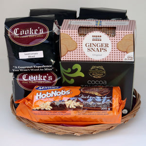 A thin wicker tray holding a selection of products, including: 2 1-pound bags of Cooke's coffee, 2 half-pound bags of Cooke's coffee, a sleeve of cookies, a box of cookies, and a box of truffles. Exact products vary by order.