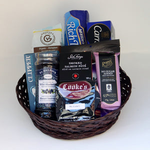 A brown wicker basket holding a selection of products, including: a box of tea, a jar of jam, a sleeve of cookies, a sleeve of biscuits, a box of crackers, a tin of salmon paté, a chocolate bar, a bag of chocolate, and a 1-pound bag of Cooke's coffee. Exact products vary by order.