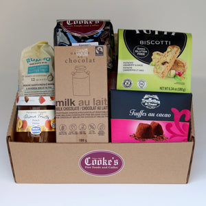 A brown rectangular basket with the burgundy Cooke's logo, holding a selection of products including: a bag of pasta, a jar of jam, a box of truffles, a bag of biscotti, a one-pound bag of Cooke's coffee, and a chocolate bar. Exact products vary by order.