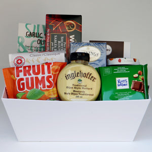 A white rectangular basket holding a selection of products, including: a bag of candy, a bag of chips, a bag of olives, a box of shortbread, jar of mustard, a box of tea, a box of chocolate, a jar of jam, and a chocolate bar. Exact products vary by order.