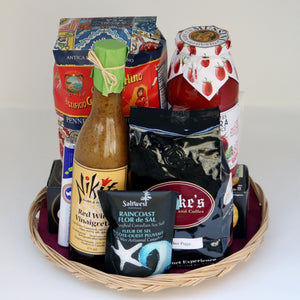 A thin wicker tray holding a selection of products, including: a bag of rice, a jar of pasta sauce, a box of crackers, a bag of salt, a sleeve of mints, a bottle of dressing, and a one-pound bag of Cooke's Coffee. Exact products vary by order.