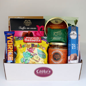 A white rectangular basket with the burgundy Cooke's logo, holding a selection of products including: a bag of candy, a tin of candy, box of truffles, a bag of chips, a box of cookies, and 3 assorted chocolate bars. Exact products vary by order.