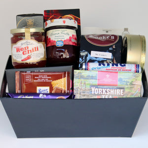 A black rectangular basket holding a selection of products, including: a jar of jelly, a jar of jam, a 1-pound bag of Cooke's coffee, a bag of olives, a box of truffles, a box of crackers, a tin of candy, a box of cookies, a box of tea, a sleeve of mints, and 2 assorted chocolate bars. Exact products vary by order.