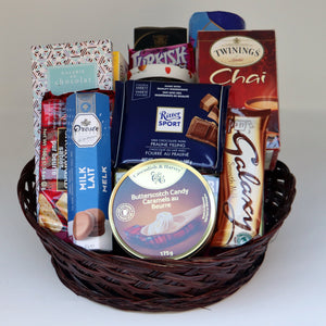 A brown wicker basket holding a selection of products, including: a tin of candy, 3 assorted boxes of tea, a jar of jam, a box of crackers, a sleeve of cookies, and 4 assorted chocolate bars. Exact products vary by order.