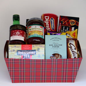 A red-tartan rectangular basket holding a selection of products, including: a jar of jelly, a jar of jam, a bottle of cordial, a box of tea, a box of salted fudge, a sleeve of cookies, a box of shortbread, and 3 assorted chocolate bars. Exact products vary by order.
