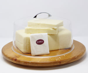 Cooke's white cheddar in three large blocks, with one small piece wrapped in white cheese paper and stickered with the Cooke's burgundy logo, all under a clear dome with metal handle and sitting on a round wooden board.