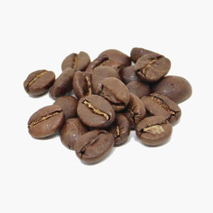 A small pile of coffee beans brown in colour from roasting, on a white background.