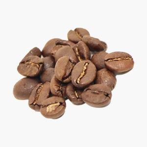A small pile of coffee beans light brown in colour from roasting, on a white background.