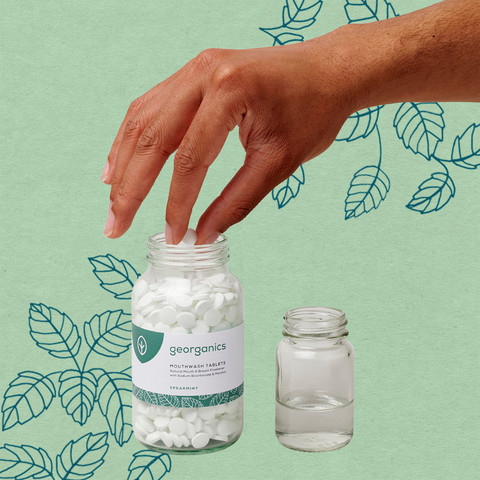 Hand reaching for our Spearmint Mouthwash Tablets, in front of leaves on a green kraft background.