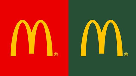 Mcdonalds old red logo next to their new green logo.