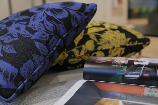 Shaku upcycled Italian silk scarf cushions beside a magazine