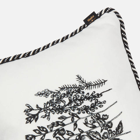 Details of cord piping on white embroidered cushion