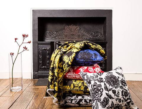 Stack of Floral Cushions in front of fireplace