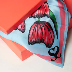 Floral scarf overhanging from coral gift box