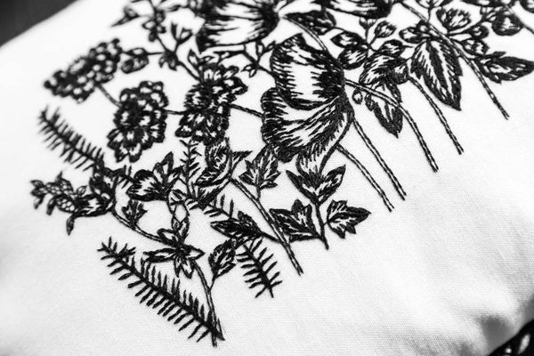 Details of embroidery on white embroidered cushion