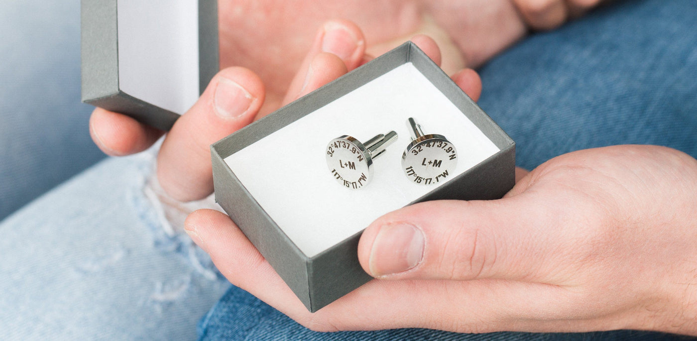 man holding personalized silver cufflinks in a gift box