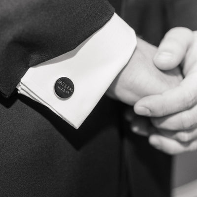 Customer's wedding photo showing a pair of Love, Georgie personalized cufflinks engraved with couple's names and wedding date.