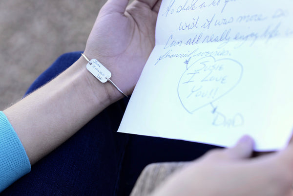 Woman wearing personalized bracelet engraved with handwriting.