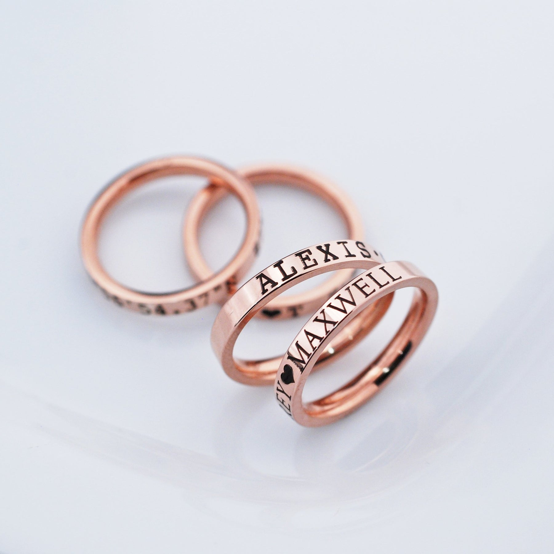 Personalized rose gold rings engraved with names.