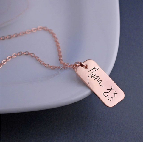 "Rose gold necklace with ""Nana XXOO"" engraved in child's handwriting on pendant."