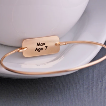 "Reverse side of engraved child's artwork bracelet, showing child's name and age ""Max Age 7""."