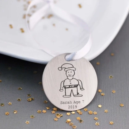 Christmas ornament engraved with child's drawing of Santa, child's name, child's age, and year.