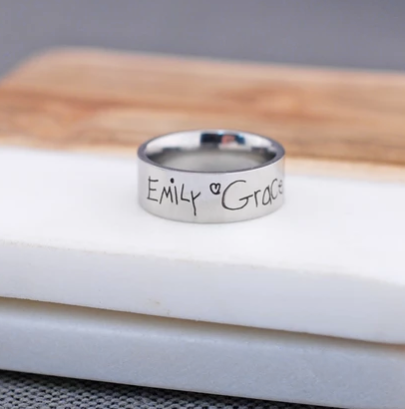 Two children's signatures engraved on a stainless steel ring.