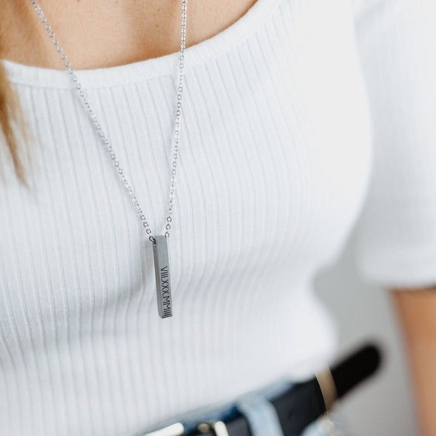 Anniversary gift idea: couple's initials engraved on a sleek and modern vertical bar pendant, suspended on an adjustable chain necklace. The female model is wearing the necklace with the stainless steel finish option. Made by Love, Georgie.