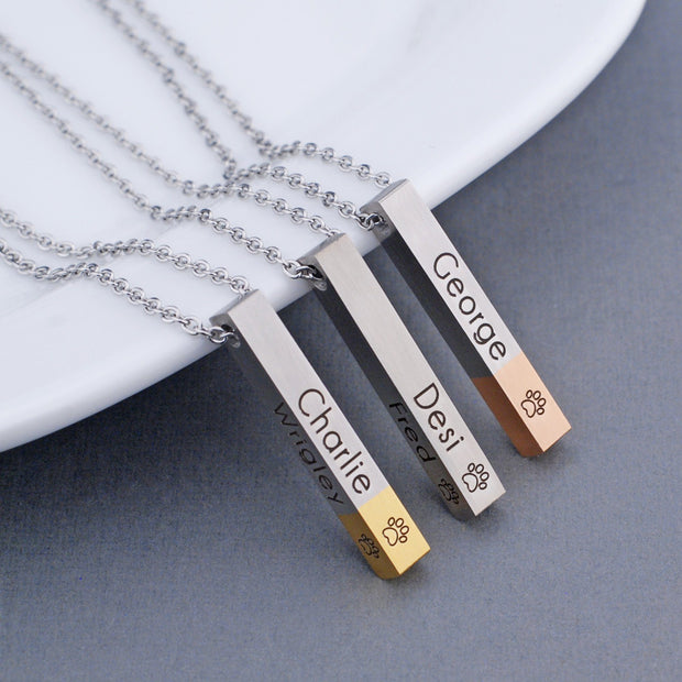 Three versions of our Pet Paw Print Bar Necklace. Engraved with your pet's name and a small paw print. Pendant is 4-sided and can hold up to four pets' names. Stainless steel vertical bar pendant can be tipped with yellow gold or rose gold. Made by Love, Georgie.