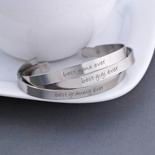"A trio of personalized stainless steel cuff bracelets read ""best gigi ever"" and ""best grammy ever"" and ""best nana ever"". A 50 character message can be engraved on the back. Made by Love, Georgie."