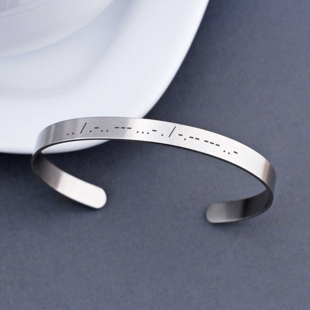 Wear a secret message in plain sight with our Morse Code Cuff Bracelet. It is engraved with the morse code translation of up to 20 characters. The adjustable stainless steel bracelet can also hold a second morse code message of 20 characters or a message of up to 50 standard characters on the inside surface. Made by Love, Georgie.
