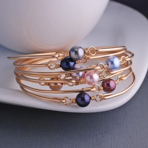 stacked gold and Swarovski pearl bracelets