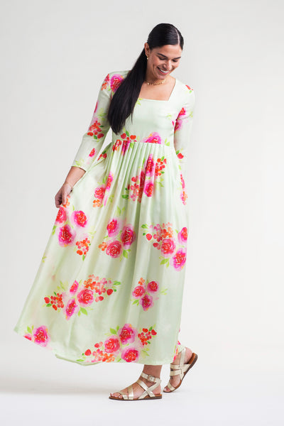 Woman wearing a mint green color silk maxi dress with watercolor floral print