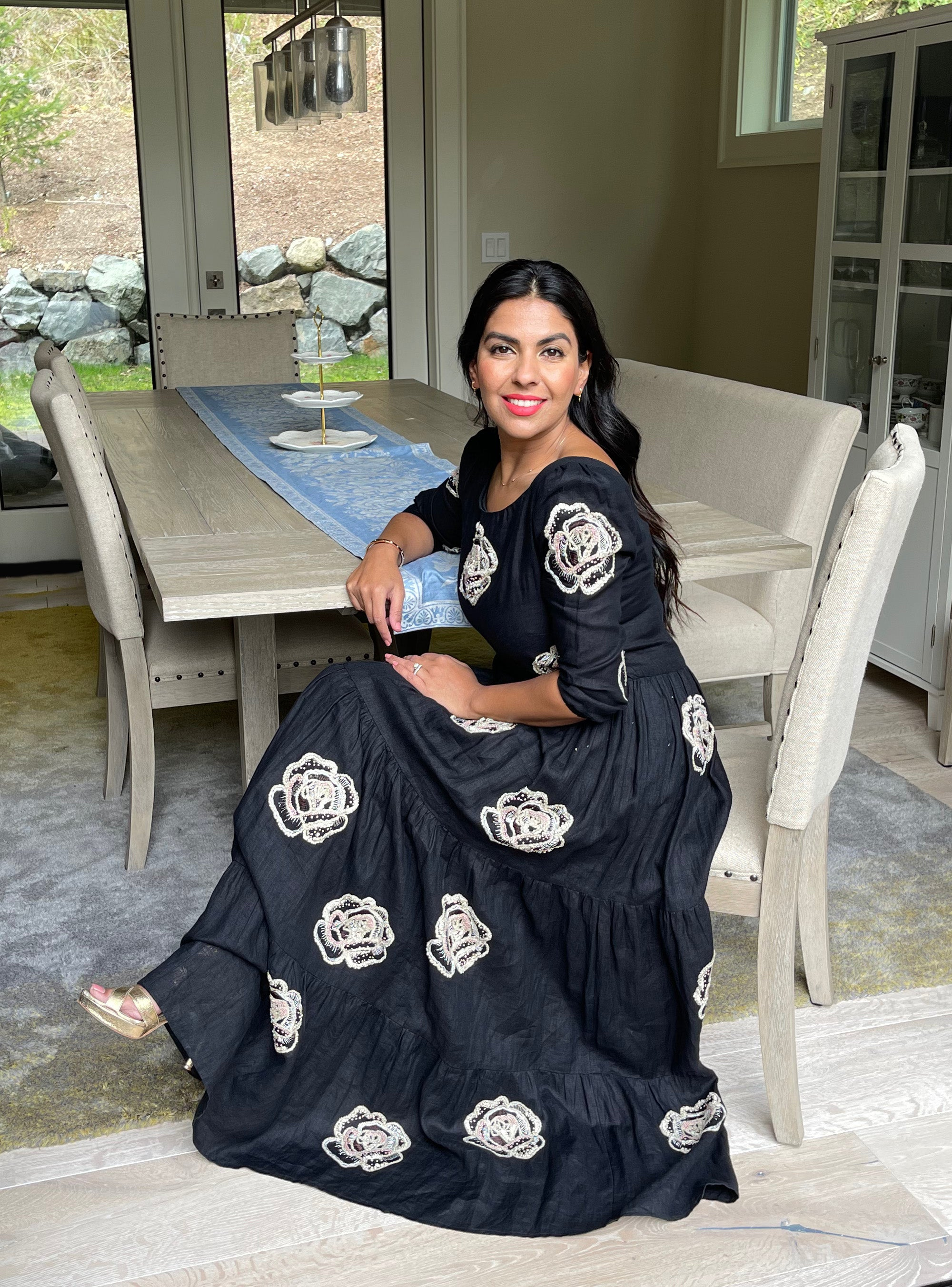 Woman wearing black linen dress with hand embroidery and pockets