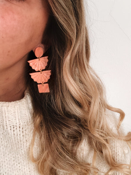 woman with blonde hair coral orange color polymer clay earrings handmade with gold plated silver earring post