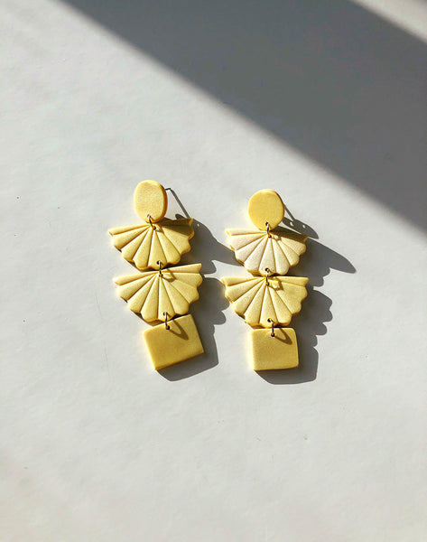 shimmery yellow handmade polymer clay earrings flat lay white background