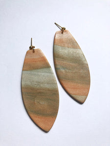 beige marbled texture polymer clay earrings with a surf board shape