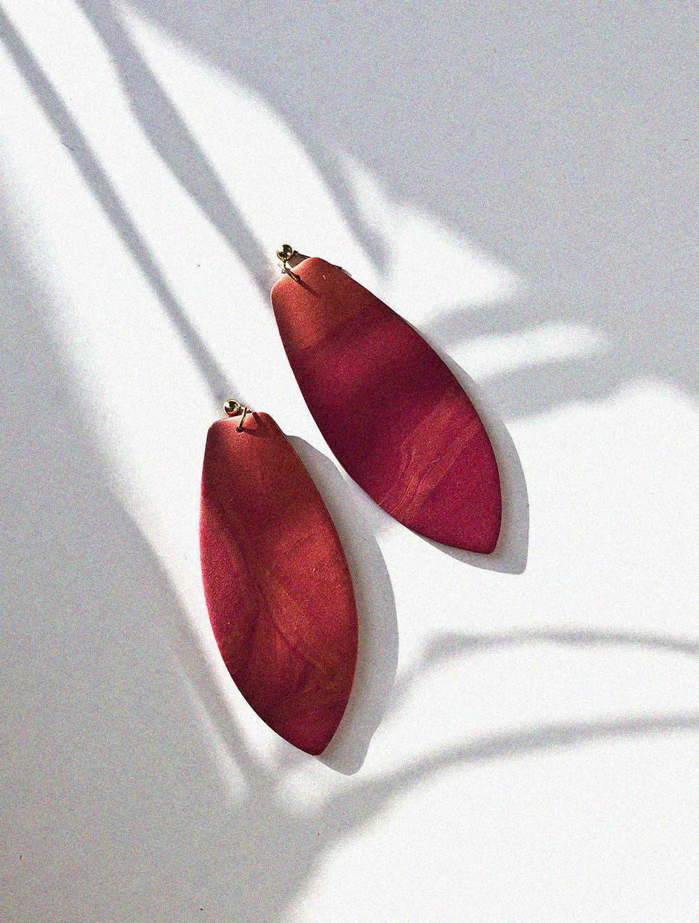 red and pink texture polymer clay earrings with a surf board shape
