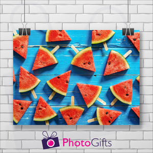 White painted brick wall with a landscape picture hanging from two clips. The picture is of some weatherbeaten wooden boards that have been painted a sky blue with triangles of water melon on lolly sticks all over the boards. As produced by Photogifts.co.uk