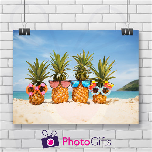 White painted brick wall with a landscape picture hanging on the wall from two clips. The picture is of four pineapples sitting on a sandy beach with blue sky and ocean in the background and the start of a small green hill in the back. All four pineapples are wearing different types of funny sunglasses. As produced by Photogifts.co.uk