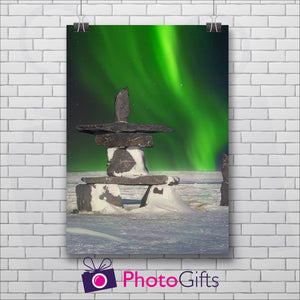 White painted brick wall with a portrait picture hanging by two metal clips. The picture is of a snowy land with a stone sculpture with some snow on and in the night sky behind is the Northern Lights showing in vivid green. Picture as produced by Photogifts.co.uk