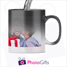 Load image into Gallery viewer, Personalised 10oz black colour change mug with your own choice of image shown in the stage where half the mug has received hot liquid and is in the process of revealing the image. As produced by Photogifts.co.uk