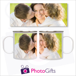white plastic mug shown from the right and the left with the picture of a mum being kissed on either side of her face by two children. Above the mug is a full depiction of the picture shown on the mug. Mug as supplied by Photogifts.co.uk