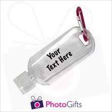 "Load image into Gallery viewer, Close up image of a small 50ml clear plastic travel bottle together with a pink carabiner. Bottle is personalised with ""Your text here"" in black text. As supplied by Photogifts.co.uk"