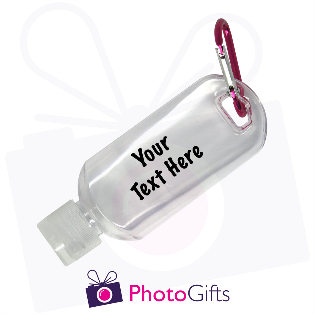 Close up image of a small 50ml clear plastic travel bottle together with a pink carabiner. Bottle is personalised with