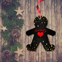 Load image into Gallery viewer, Dark wooden background with a Christmas Garland stretched out on the Left hand side from top to bottom. On the garland are some wooden strs and fir cones along with some dark red berries. To the right of the garland is a Christmas Decoration in the shape of a gingerbread man with a red ribbon. The decoration is mainly black with golden stars over the head and leg and feet area. In the centre is a red heart with the word family above. Decoration as supplied by Photogifts.co.uk